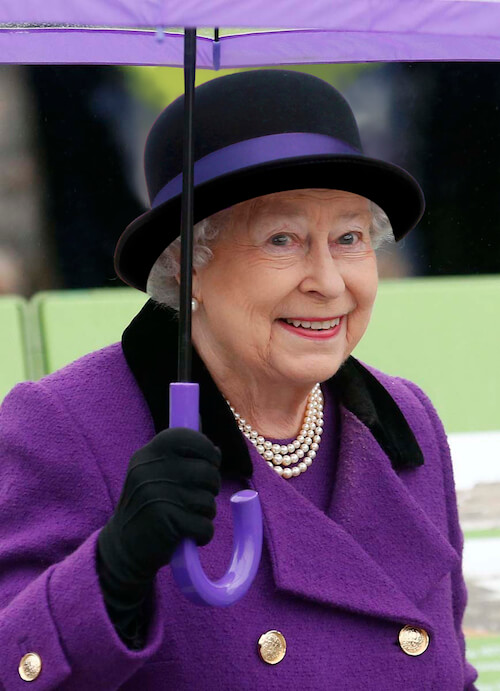 The queen wearing Alfreds hat and matching purple outfit